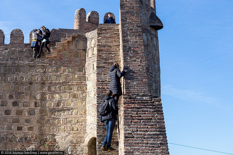 Люди поднимаются на стену крепости Нарикала в Тбилиси