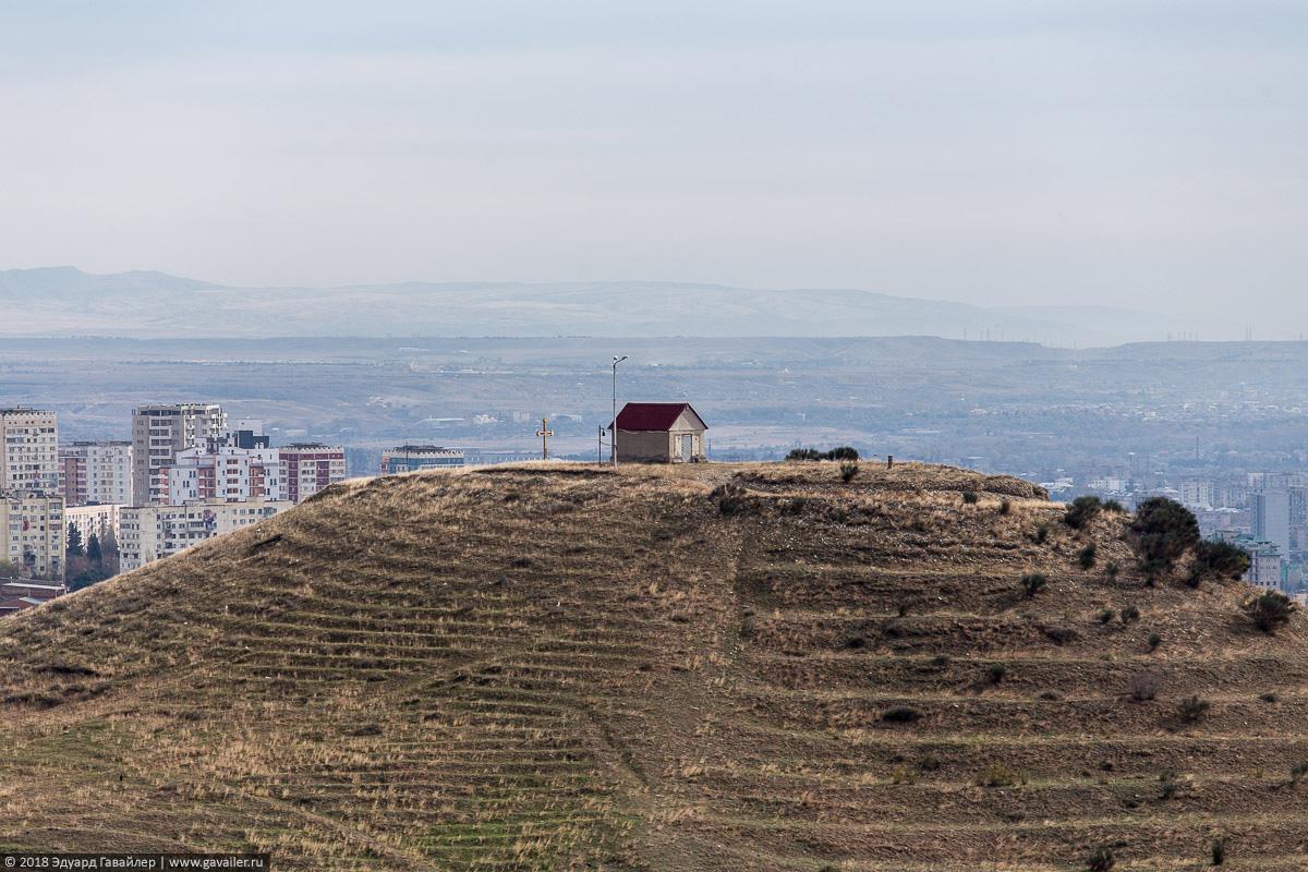 Одиночный домик и крест на возвышенности под Тбилиси
