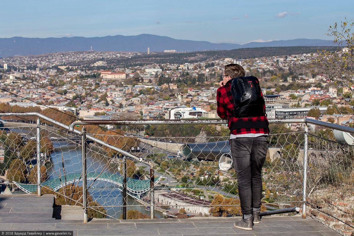 Турист на смотровой площадке крепости Нарикала смотрит на Тбилиси